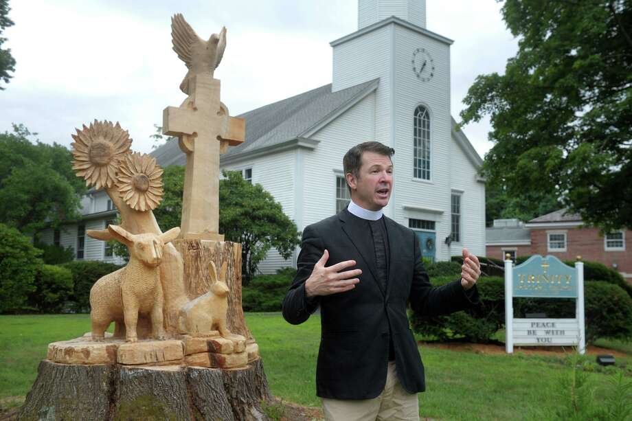 Rev. Alan Murchie speaks during an interview next to the new sculpture carved out of the truck of an old Maple tree in front Trinity Episcopal Church, in the Nichols neighborhood of Trumbull, Conn. July 24, 2020. Photo: Ned Gerard / Hearst Connecticut Media / Connecticut Post