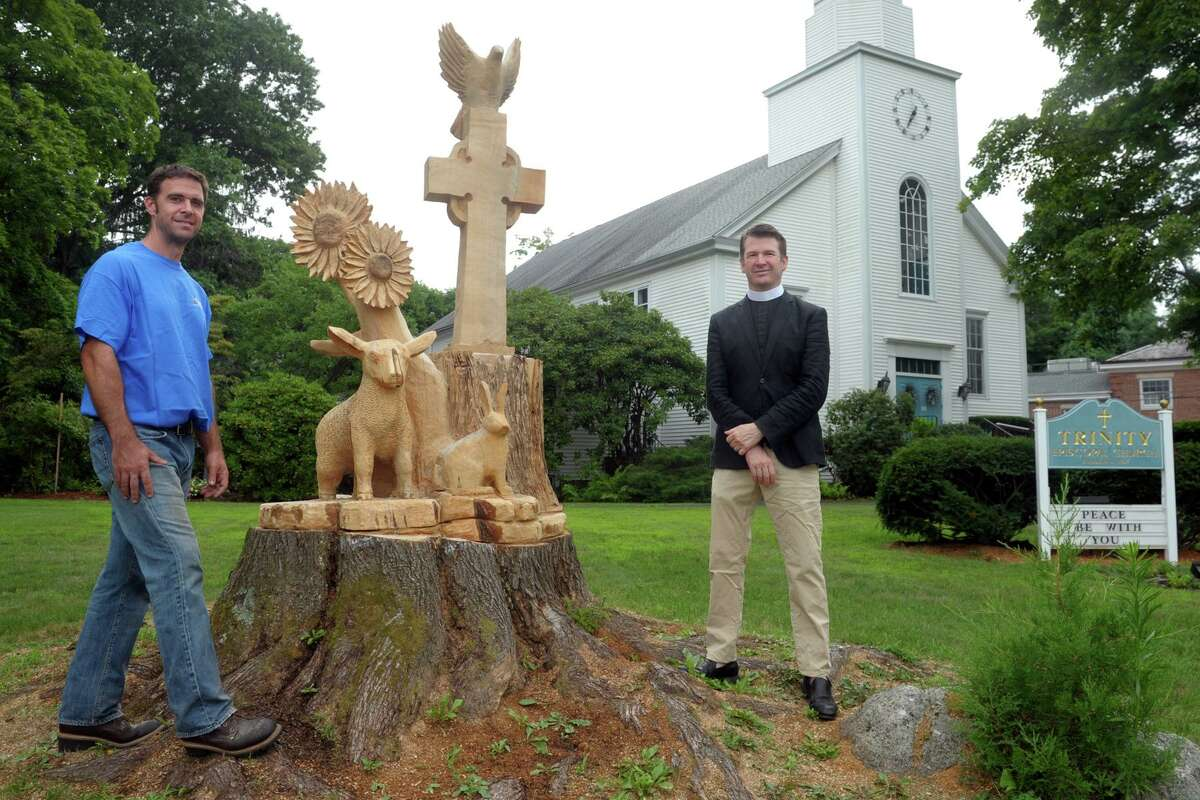 Sculptor Jared Welcomes, left, and Rev. Alan Murchie stand next to the new sculpture carved out of the truck of an old Maple tree in front Trinity Episcopal Church, in the Nichols neighborhood of Trumbull on Friday.