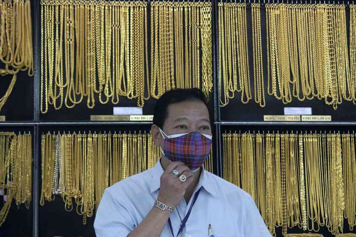 FILE - In this April 16, 2020, file photo, a Thai shopkeeper adjusts his face mask at a gold shop in Bangkok, Thailand. The price of gold surged more than $30 on Monday, July 27, 2020 to over $1,926 per ounce as investors step up buying of the precious metal often sought in times of uncertainty. Gold was trading at $1,926.20 by early afternoon in Asia, up 1.5%, after surging over the weekend.