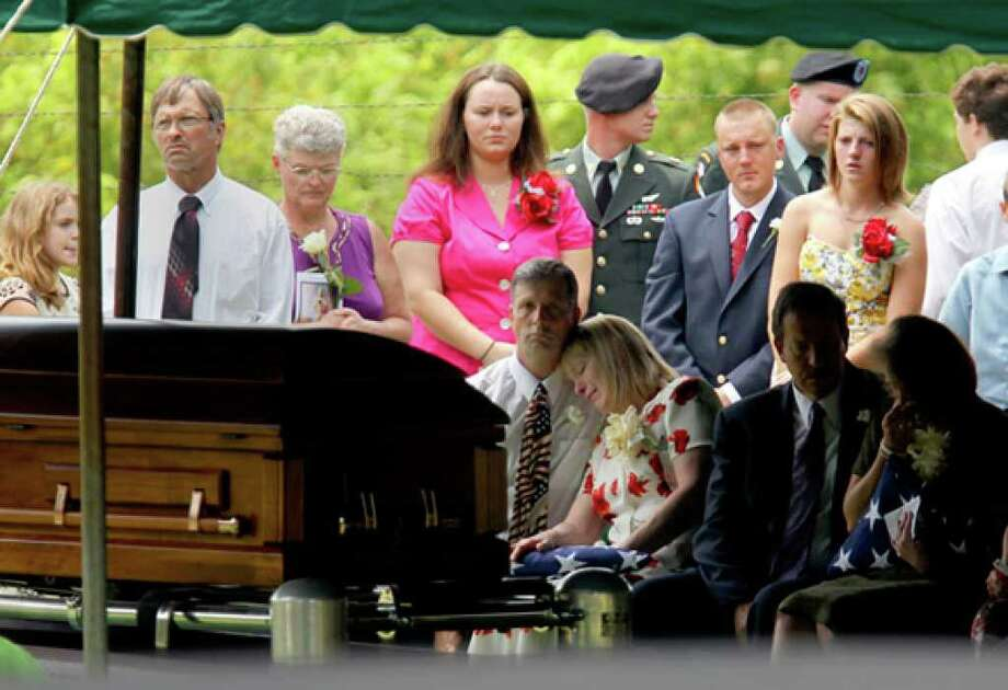 Family, friends and loved ones attend the burial of Army Pfc. Benjamen Chisholm. Seated are Chisholm's father, Glenn Chisholm; his stepmother, Lynn Chisholm; his stepfather, Skip Doerr; and his mother, Linda Reynolds.