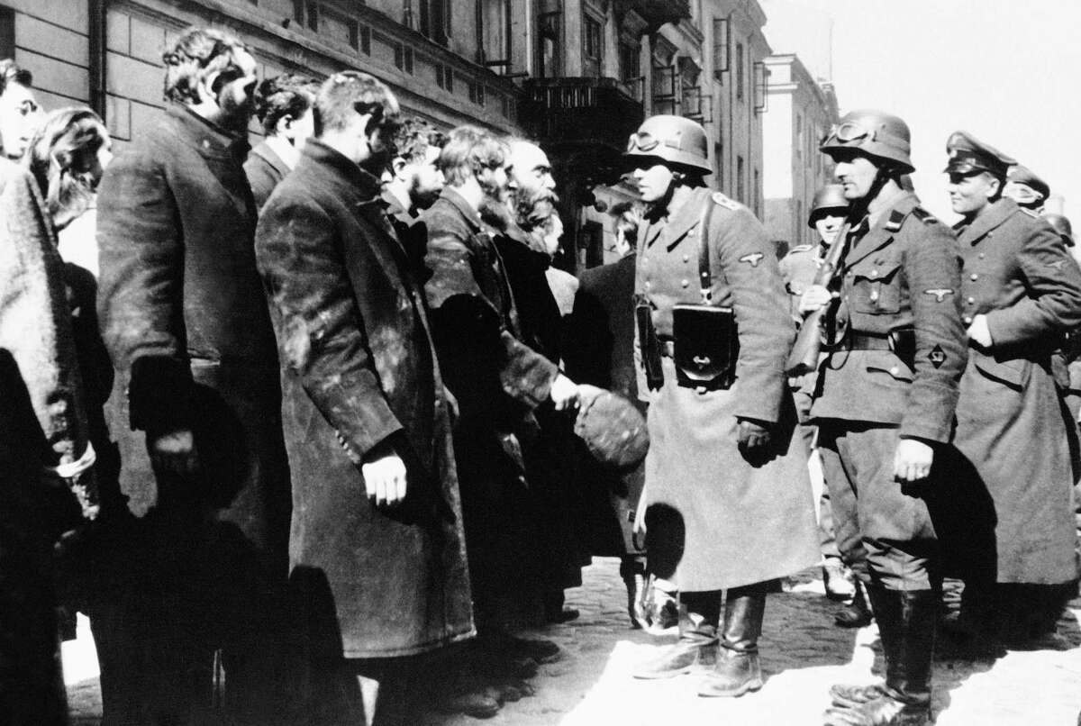 This 1943 file photo shows Nazi officers talking with citizens of the Warsaw ghetto in Poland. An Associated Press investigation found dozens of suspected Nazi war criminals and SS guards collected millions of dollars in Social Security payments after being forced out of the United States. (AP Photo, File)