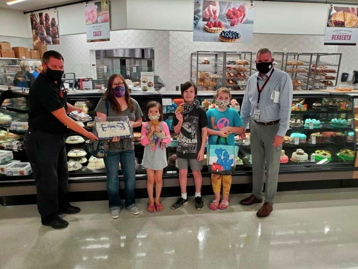 """Shar Mohr, poses for a photo as she receives a birthday surprise from members of management at the Bad Axe Meijer store. Mohr is something of a Meijer superfan, and she decided to share her enthusiasm by starting social media pages dubbed """"The Bad Axe Meijer Mom."""" (Courtesy Photo)"""