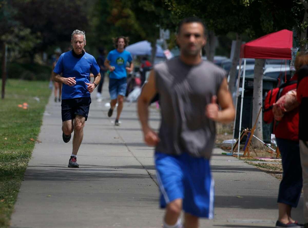 Joggers run laps around Lake Merritt in Oakland, Calif. on Thursday, July 16, 2020.