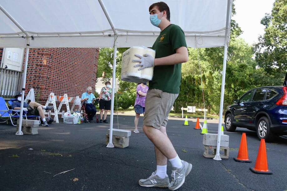 Gary Stewart, 17, of Fairfield carries a donation item at the Boy Scouts' food drive for Operation Hope at its food pantry on Saturday, July 26, 2020, in Fairfield, Conn. Photo: Jarret Liotta / Jarret Liotta / ©Jarret Liotta 2020