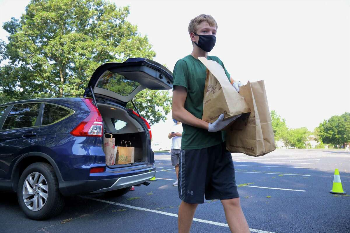 Campbell Treschuk, 14, of Fairfield totes some groceries at the Boy Scouts' food drive for Operation Hope at its food pantry on Saturday, July 26, 2020, in Fairfield, Conn.