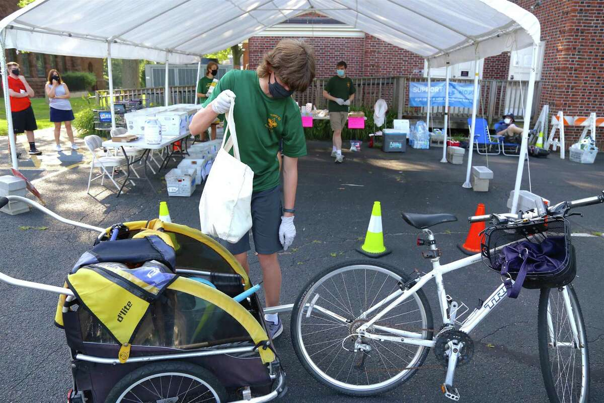 Simon Weber, 15, of Fairfield gets stuff being dropped off by bicycle at the Boy Scouts' food drive for Operation Hope at its food pantry on Saturday, July 26, 2020, in Fairfield, Conn.