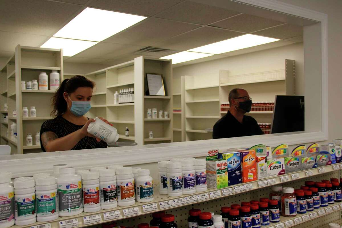 Kara Gehring, left, and Michael Delpiere, right, work at the new Ubly Pharmacy on opening day. (Robert Creenan/Huron Daily Tribune)