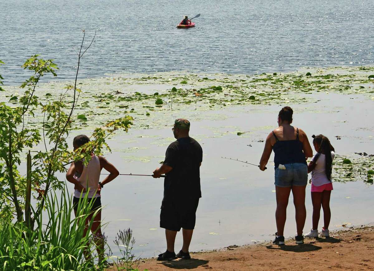 A family is seen fishing while a kayaker heads out for a paddle on Round Lake on Monday, July 27, 2020 in Round Lake, N.Y. (Lori Van Buren/Times Union)