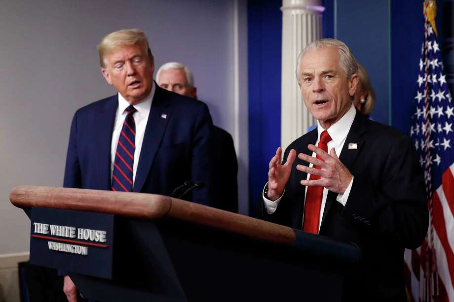 "FILE - In this Friday, March 27, 2020 file photo, White House adviser Peter Navarro speaks about the coronavirus in the James Brady Press Briefing Room in Washington, as President Donald Trump listens. Navarro, Trump's top assistant for trade and manufacturing policy, said in a March 19, 2020 email that he would soon be ""flooding"" the office of Dr. Robert Kadlec, whose job is to help guide the country through public health emergencies, with contracts for possible treatments. ""Your shop is now officially a bottleneck,"" Navarro told the assistant secretary for preparedness and response at the Department of Health and Human Services. (AP Photo/Alex Brandon) / Copyright 2020 The Associated Press. All rights reserved."