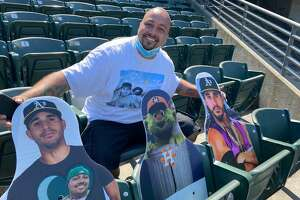 Oakland A's fan Bryan Johansen poses with the three cardboard cutouts he placed in the stands at the Oakland Colisuem.