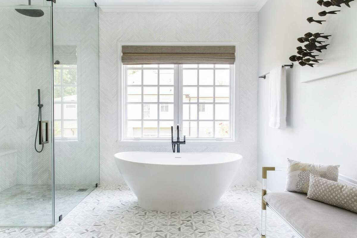 For this spa bathroom in Houston, Oakland-based interior designer Kelly Finley positioned a freestanding soaking tub atop a patterned tile floor and beside a walk-in shower.