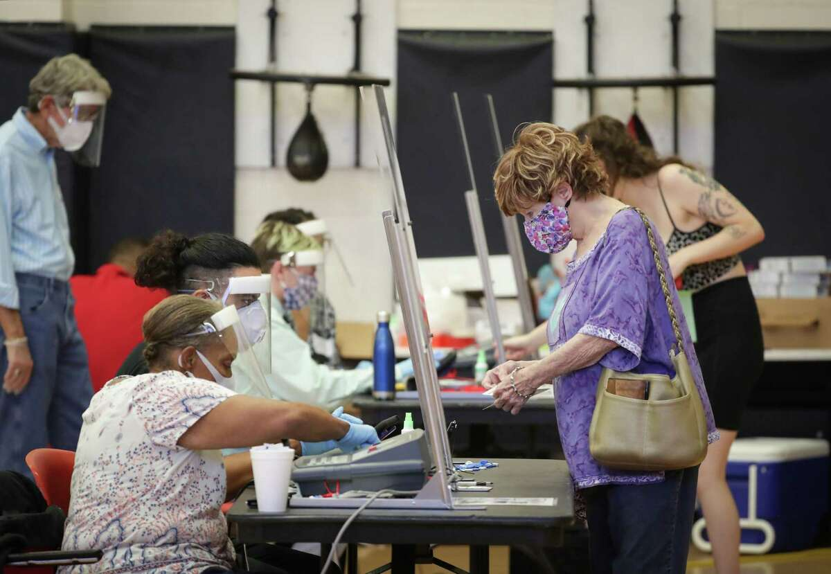 Voters check in before voting at the Metropolitan Multi-Services Center, 1475 West Gray St., Tuesday, July 14, 2020, in Houston.