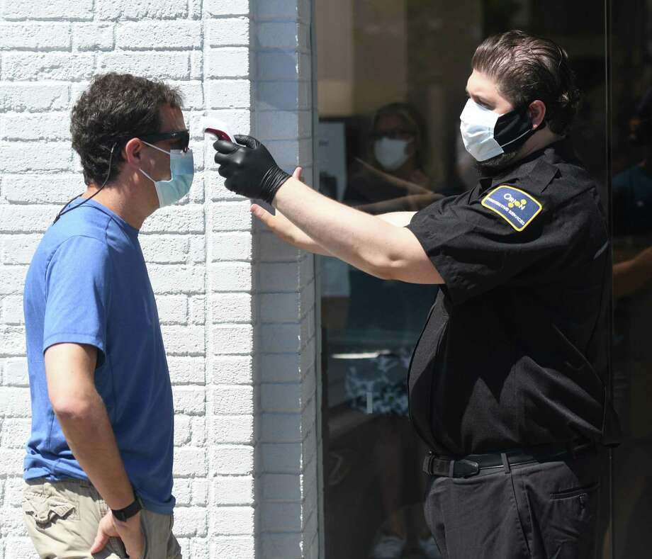 A customer gets his temperature taken by security before entering the Apple store on the day of its reopening in Greenwich, Conn. Wednesday, June 17, 2020. The Apple Store reopened with other businesses of the second phase of reopenings in Connecticut, including nail salons, gyms, limited indoor dining, pools, tattoo parlors and more. Photo: Tyler Sizemore / Hearst Connecticut Media / Greenwich Time