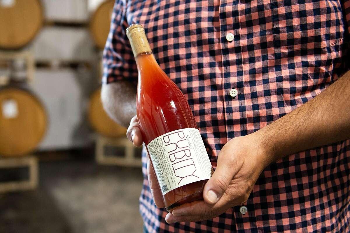 Noel Diaz, wine maker of Purity Wines, holding a bottle of wine in his tasting room on July 24, 2020 in Richmond, Calif.