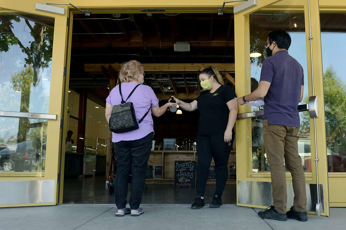 Grace Hastings, center, greets customers as she provides them with hand sanitizer before entering Castro Valley Market Place, open around two weeks, on July 24, 2020, in Castro Valley, Calif. So far, the market includes Castro Valley Natural Grocery, a grocery store focused on organic produce; Seven Hills Baking Co., a bakery with pastries and bread; and Baron's Quality Meats & Seafood, a butcher shop. Multiple restaurants, bars and other food shops are slated to join in the coming months.