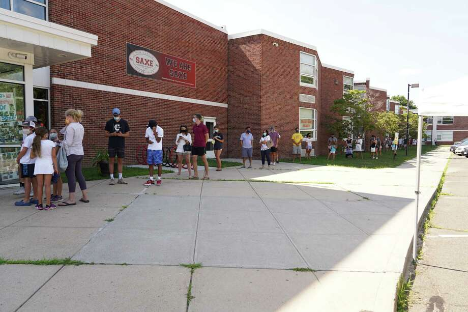 The line of people waiting to be tested for the coronavirus stretched to the far end of Saxe Middle School in New Canaan and was beginning to wrap around the west end of the building on Monday, July 27. Photo: Grace Duffield Hearst Connecticut Media