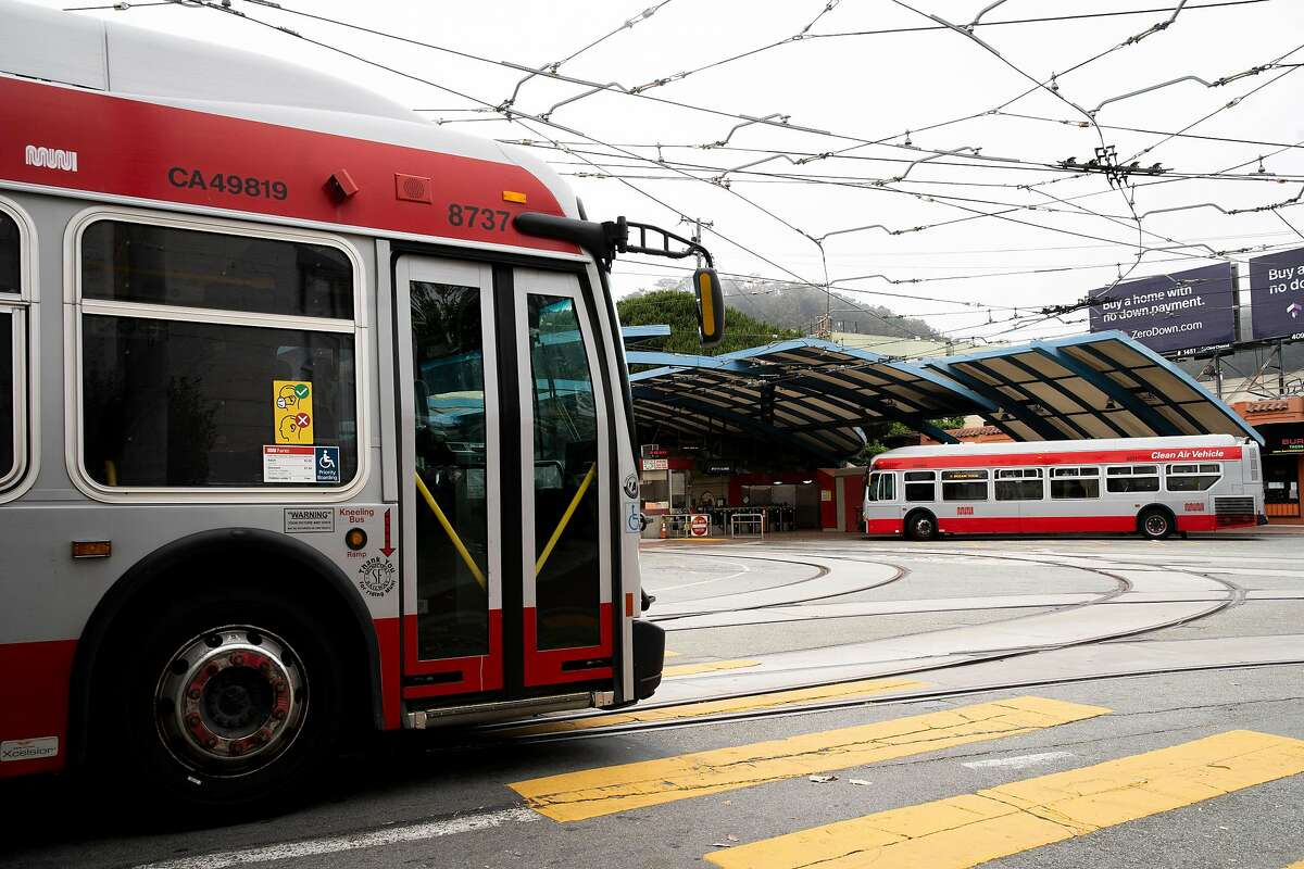 The L-Taraval Muni bus line (left) drives past the West Portal Station as the M-Ocean View bus picks up passengers outside the station on Friday, July 24, 2020, in San Francisco, Calif. The station is currently closed. Muni is reopening its Muni Metro Light Rail in August. According to the SFMTA, none of the Muni Metro lines are being eliminated and the changes are temporary emergency measures in response to the coronavirus pandemic. The measures include fewer runs, but longer trains in an attempt for physical distancing between passengers.