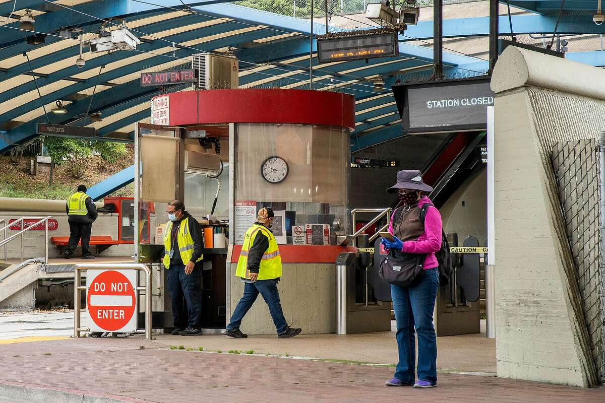 A person waits for the M-Ocean View bus line outside West Portal Station on Friday, July 24, 2020, in San Francisco, Calif. The station is currently closed. Muni is reopening its Muni Metro Light Rail in August. According to the SFMTA, none of the Muni Metro lines are being eliminated and the changes are temporary emergency measures in response to the coronavirus pandemic. The measures include fewer runs, but longer trains in an attempt for physical distancing between passengers.
