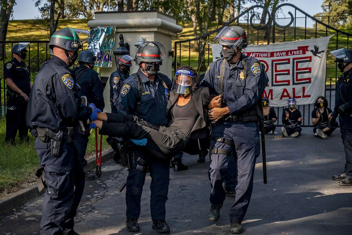 A woman protester is carried away by California Highway Patrol officers outside the gate of California Gov. Gavin Newsom's home in Fair Oaks, Calif., on Monday, July 27, 2020. Demonstrators chained themselves to a fence outside the governor's home, calling for mass inmate releases and an end to immigration transfers because of the coronavirus pandemic, as deaths mounted at a San Francisco Bay Area prison. The CHP cut the chains linking protesters to the bars of the gate at the front of the residence in suburban Sacramento after about two hours, but could not immediately say how many had been arrested. (Daniel Kim/The Sacramento Bee via AP)