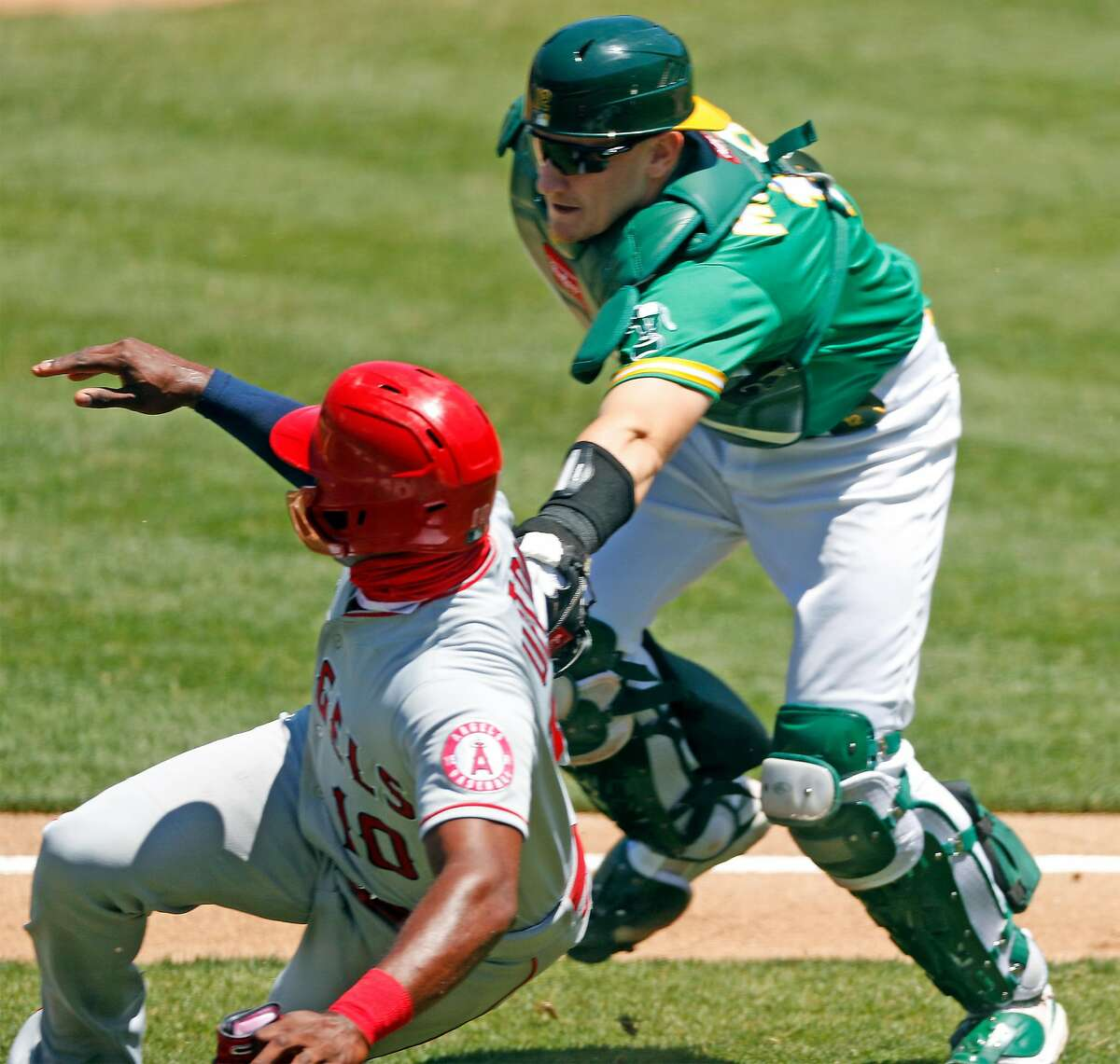 Oakland Athletics' Sean Murphy tags out Los Angeles Angels' Justin Upton during a rundown after a grounder by Albert Pujols in 4th inning during MLB game at Oakland Coliseum in Oakland, Calif., on Monday, July 27, 2020.