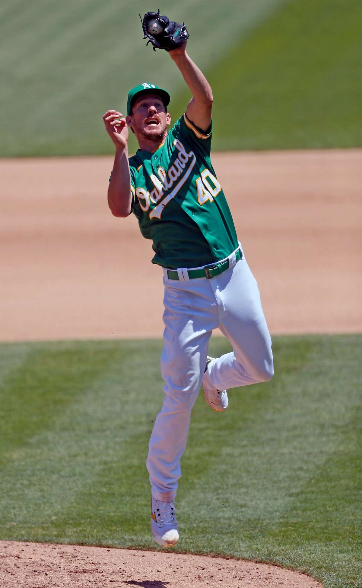With the bases loaded, Oakland Athletics' pitcher Chris Bassitt snags a comeback by Los Angeles Angels' Andrelton Simmons to start an inning-ending double play in 4th inning during MLB game at Oakland Coliseum in Oakland, Calif., on Monday, July 27, 2020.
