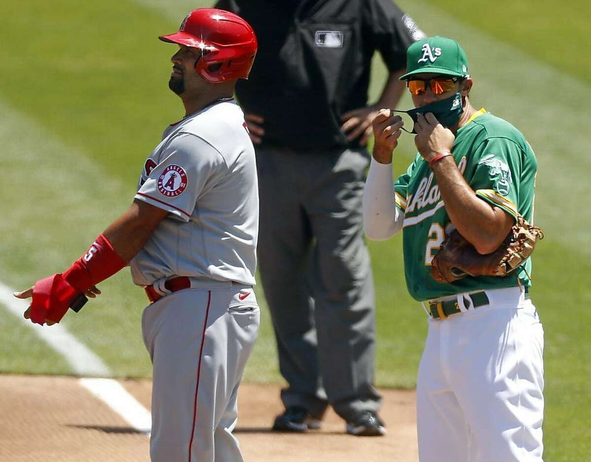 Oakland Athletics' Matt Olson puts on a mask after Los Angeles Angels' Albert Pujols singled in 2nd inning in MLB game at Oakland Coliseum in Oakland, Calif., on Monday, July 27, 2020.
