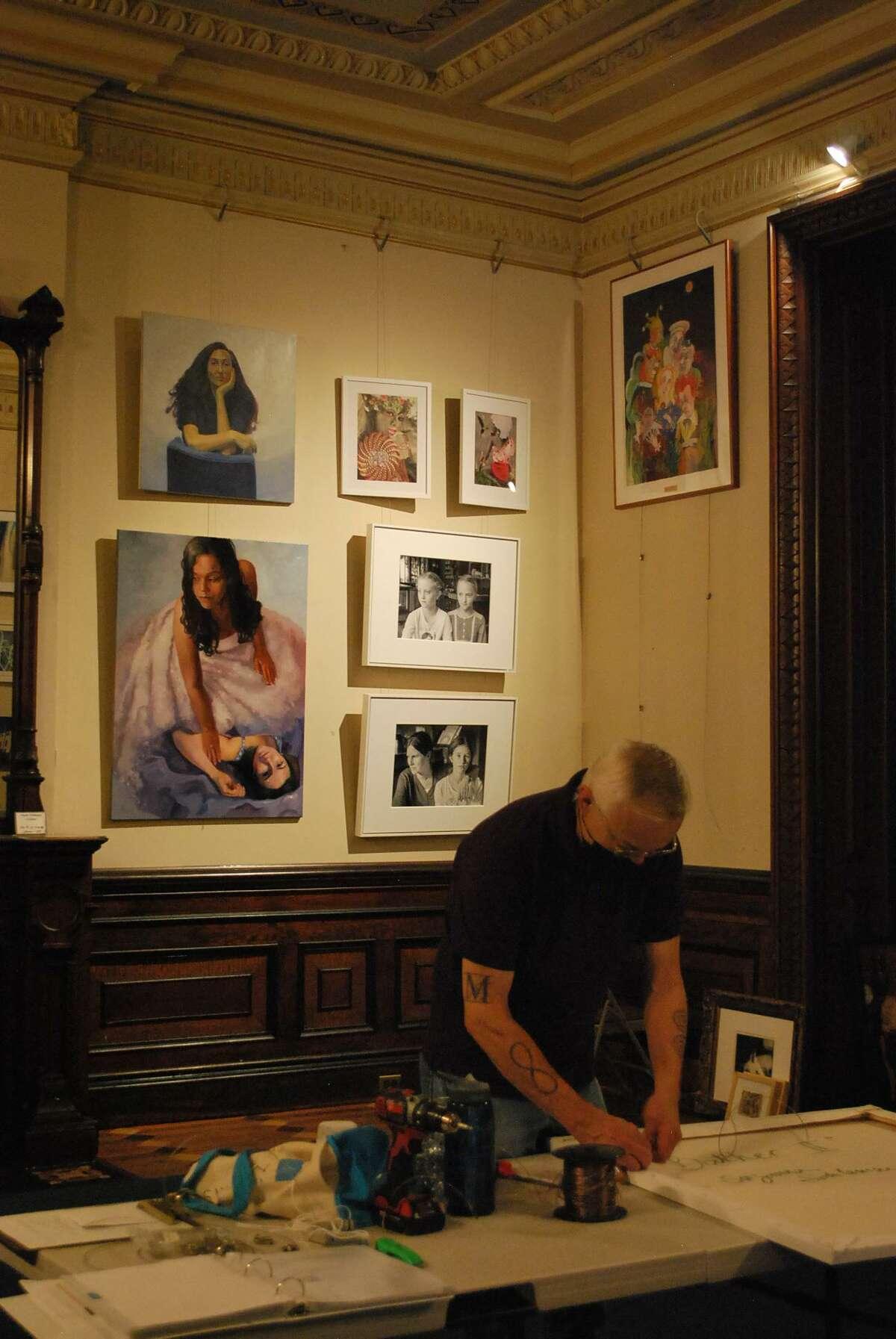 Silvermine Arts Center Executive Director Roger Mudre installs the exhibition,