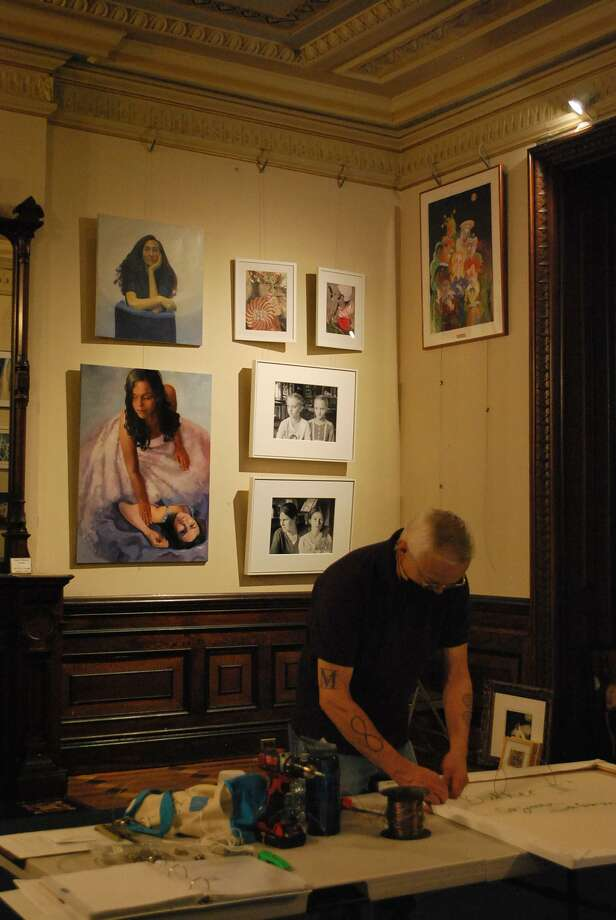 "Silvermine Arts Center Executive Director Roger Mudre installs the exhibition, ""About Women,"" in the Lockwood-Mathews Mansion Museum's Billiards Room. Photo: LMMM / Contributed Photo"