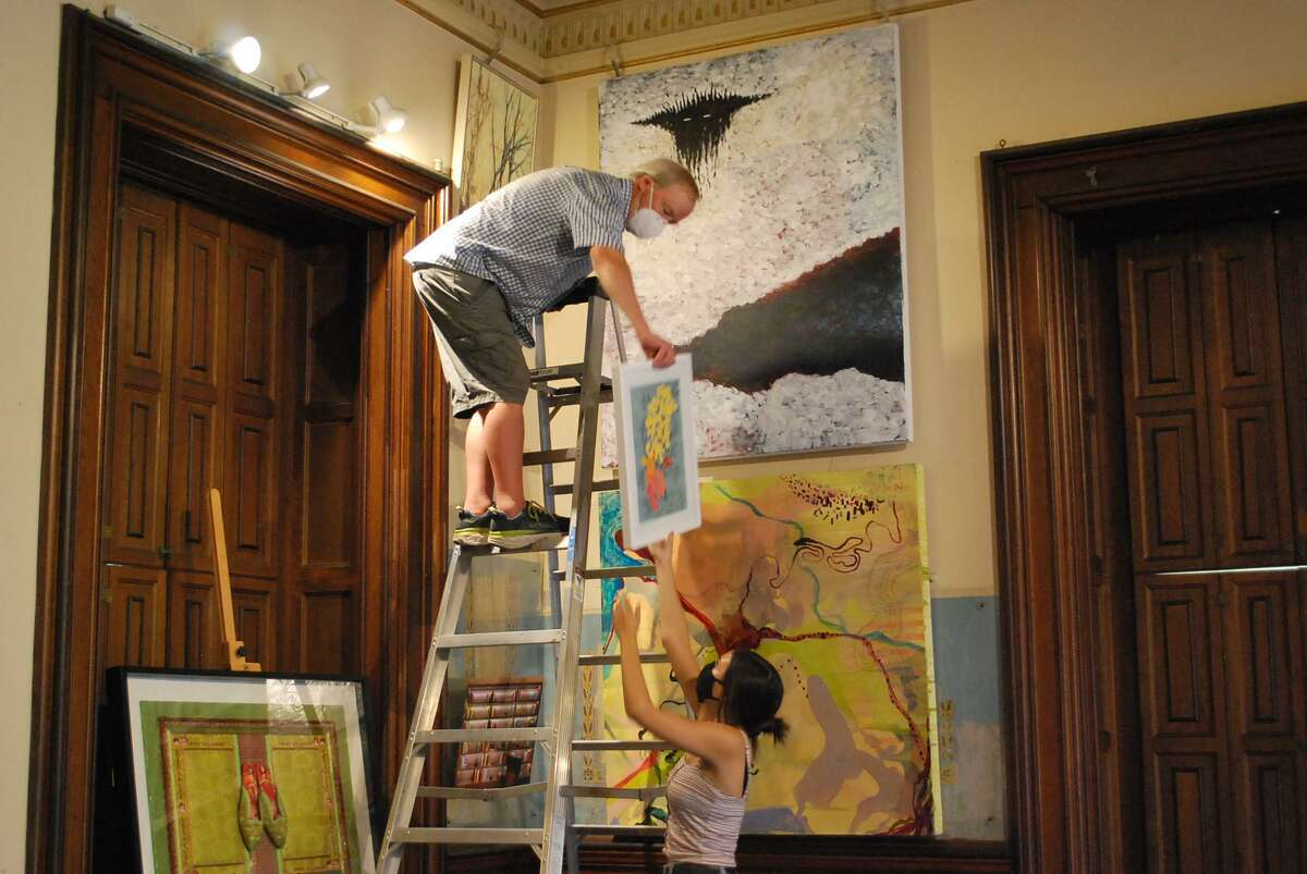 Silvermine Arts Center Gallery Assistant Emily Bockisch with Volunteer Installer John Harris in the Lockwood-Mathews Mansion Museum's Billiards Room during the installation of
