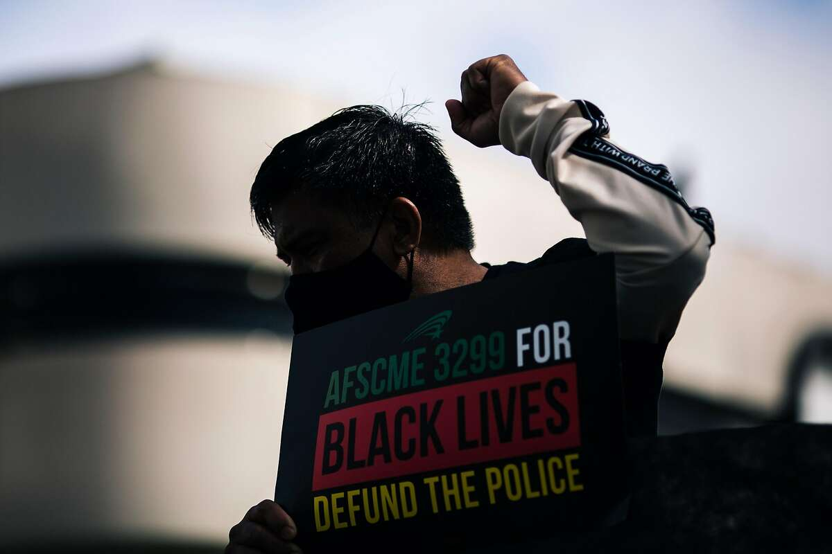 A protester raises his fist during a demonstration outside the San Francisco Police Officers Association against the POA's role in support of systematic racism and calling for the defunding of the police on Monday, July 27, 2020 in San Francisco, California.