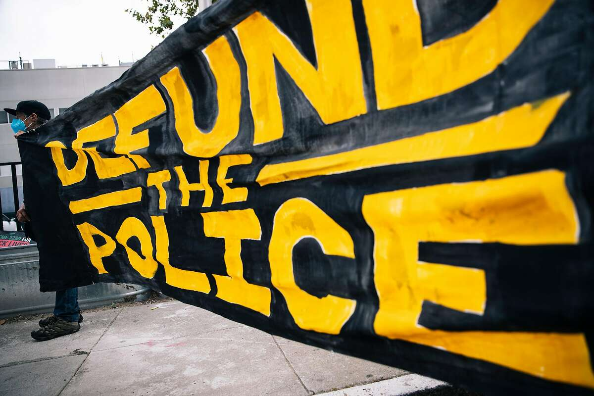 A protester holds a banner during a demonstration outside the San Francisco Police Officers Association against POA's support of racism and calling for the defunding of the police on Monday, July 27, 2020 in San Francisco, California.