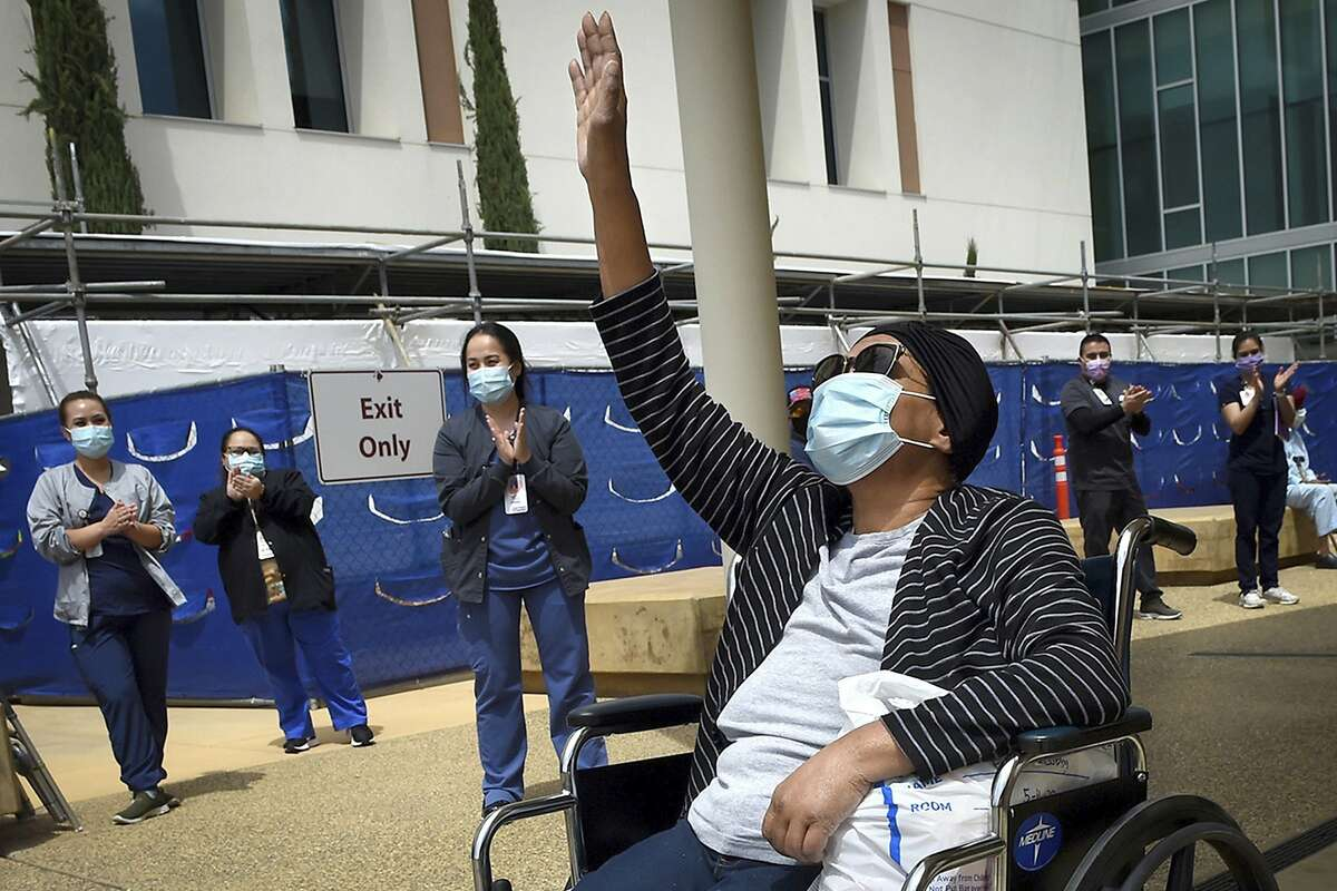 Karen Parker-Bryant, 64, raises a hand skyward after she was released from Clovis Community Hospital in Fresno, Calif., on May 19, 2020, after a month-and-a-half battle with COVID-19, including 25 days on a ventilator. Gov. Gavin Newsom said Monday, July 27, 2020, the state will spend $52 million to tackle the outbreak in eight Central Valley counties. He said the money will go toward helping improving isolation, quarantine and testing policies and to helping health care workers. (John Walker/The Fresno Bee via AP)
