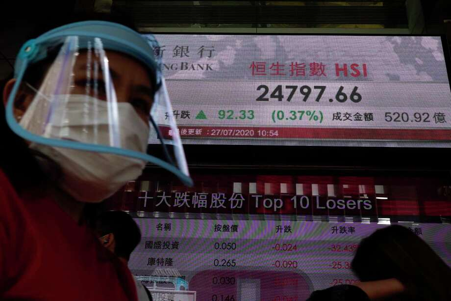 A man wearing a face mask and a shield walks past a bank's electronic board showing the Hong Kong share index at Hong Kong Stock Exchange Monday, July 27, 2020. Asian stock markets were mixed Monday amid U.S.-China tension and concern a recovery from the coronavirus pandemic might be weakening. (AP Photo/Vincent Yu) Photo: Vincent Yu / AP