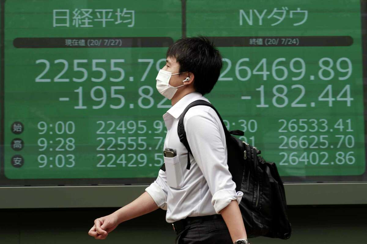 A man walks past an electronic stock board showing Japan's Nikkei 225 and New York Dow indexes at a securities firm in Tokyo Monday, July 27, 2020. Asian stock markets were mixed Monday amid U.S.-China tension and concern a recovery from the coronavirus pandemic might be weakening. (AP Photo/Eugene Hoshiko)