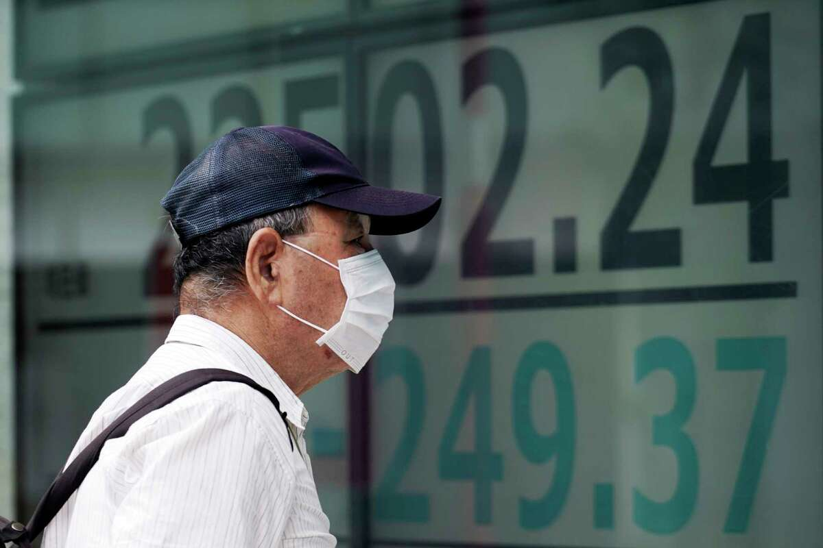 A man looks at an electronic stock board showing Japan's Nikkei 225 index at a securities firm in Tokyo Monday, July 27, 2020. Asian stock markets were mixed Monday amid U.S.-China tension and concern a recovery from the coronavirus pandemic might be weakening. (AP Photo/Eugene Hoshiko)