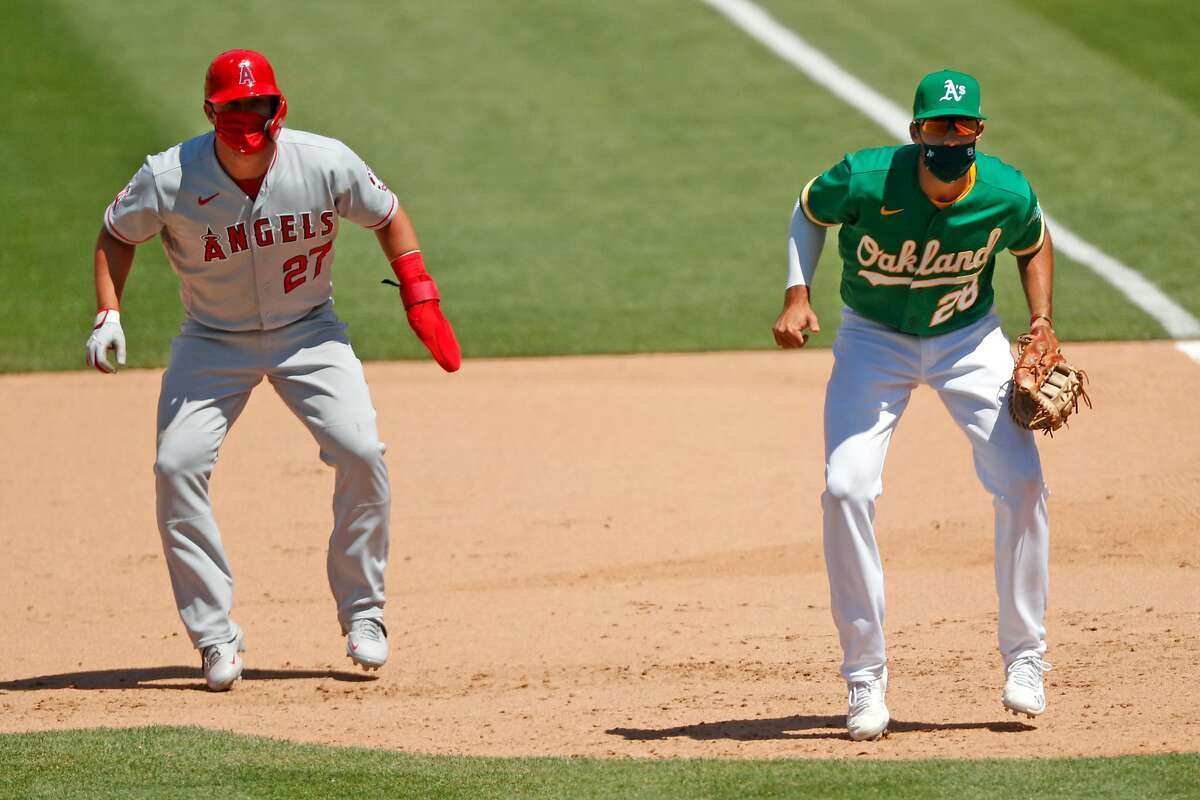 Los Angeles Angels' Mike Trout leads off 1st base next to Oakland Athletics' Matt Olson in 8th inning of MLB game at Oakland Coliseum in Oakland, Calif., on Monday, July 27, 2020.