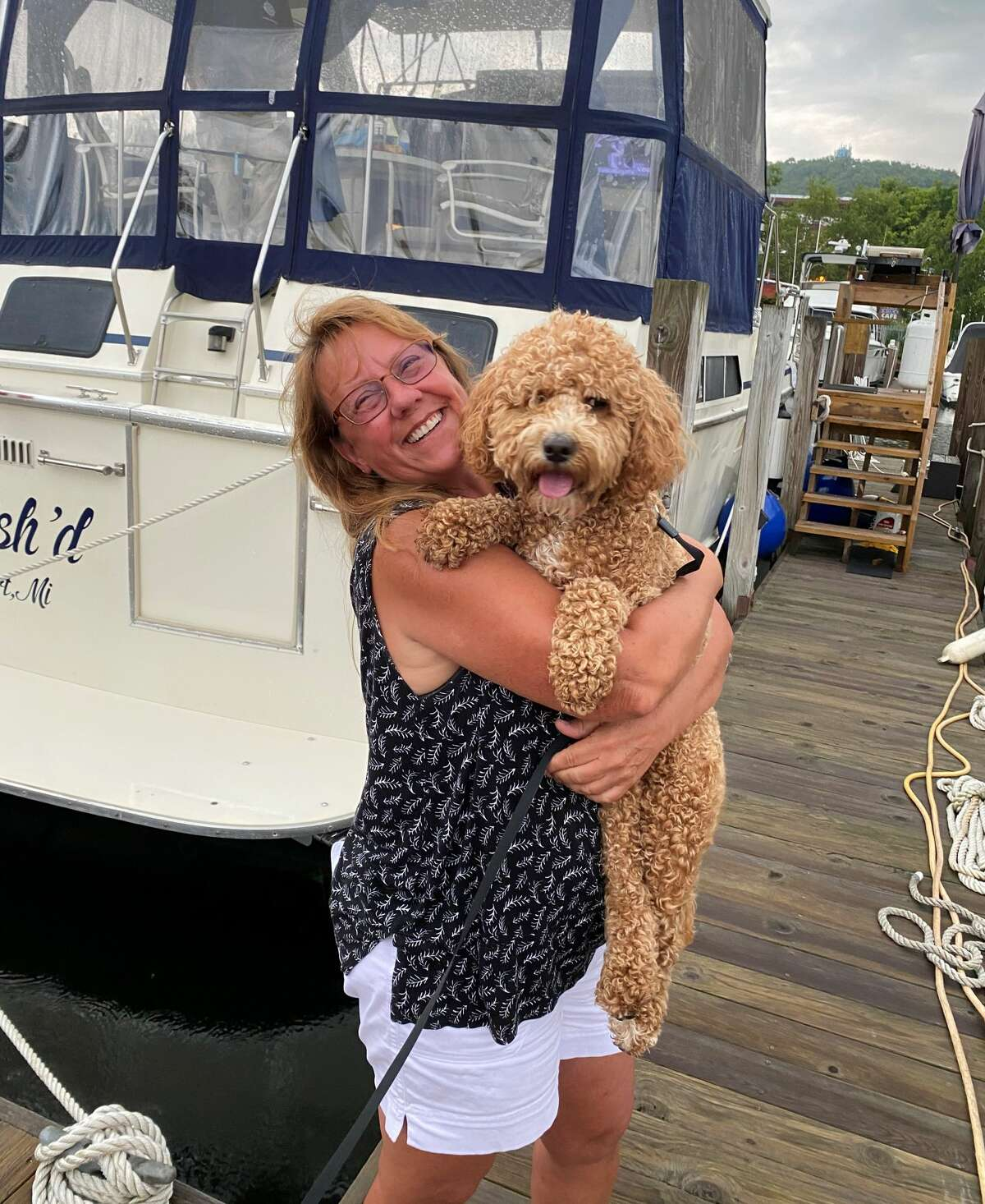 Lori Sarya holds Roxy after finding her on a difficult to travel stretch of beach near Frankfort on Sunday. Roxy had fallen overboard from her family's boat on Lake Michigan Saturday.