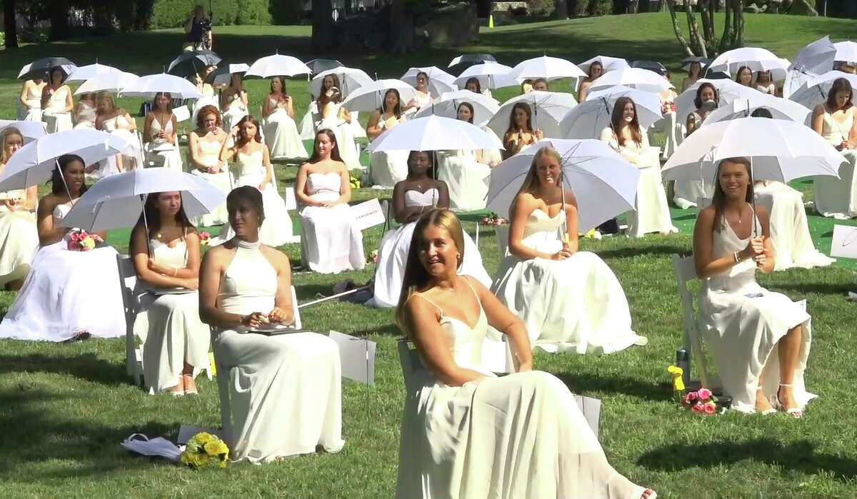 In this live video screenshot, Greenwich Academy graduates take part in the 2020 commencement ceremony in Greenwich, Conn. July 27, 2020. With temperatures reaching over 90 degrees, each graduate was given a white umbrella to shield them from Monday's blazing hot sun, therefore King encouraged them to have their