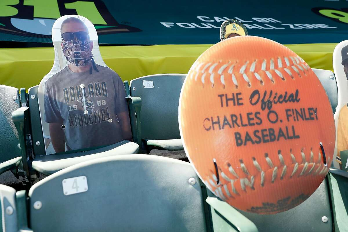 This Oakland Athletics' fan (left) is the first to win a baseball after a foul ball hit his cut out in section 126 at Oakland Coliseum in Oakland, Calif. Photographed on Monday, July 27, 2020.