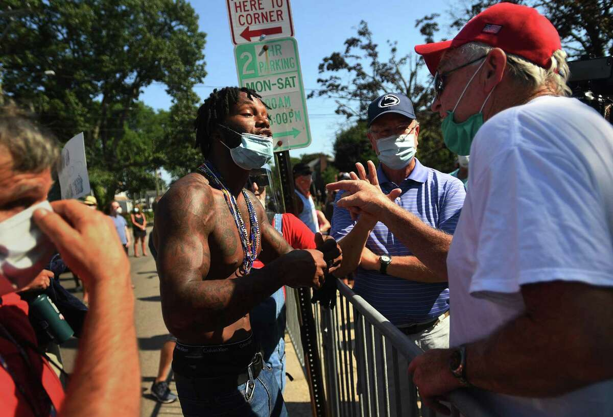 Black Lives Matter protester Byron Bigelow, left, of Bridgeport, goes face to face with police supporters outside Police Headquarters in Fairfield, Conn. on Monday, July 27, 2020. Fairfield police held a press conference in opposition to police bill HB-6004 passed by the state house of representatives last week.