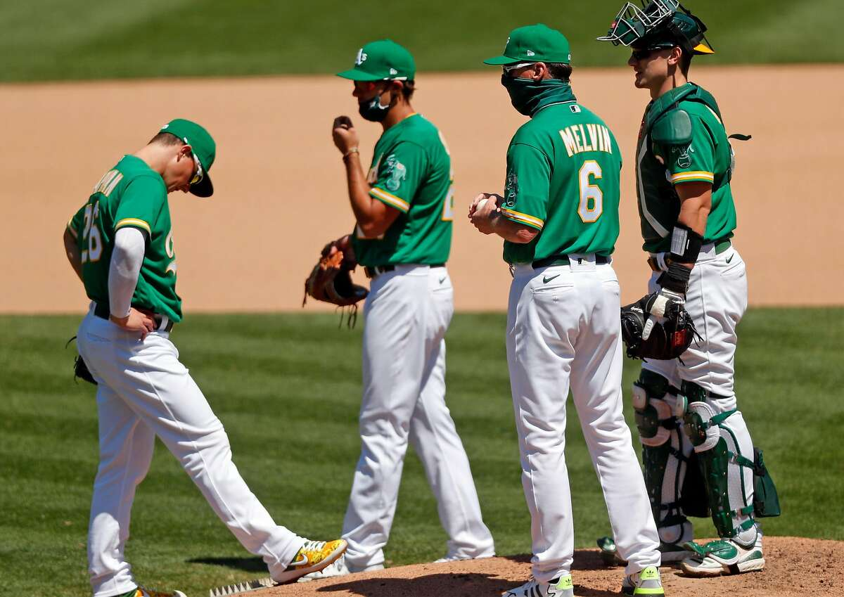 Oakland Athletics' Matt Chapman, Matt Olson, manager Bob Melvin and Sean Murphy during 7th inning pitching change against Los Angeles Angels in MLB game at Oakland Coliseum in Oakland, Calif., on Monday, July 27, 2020.