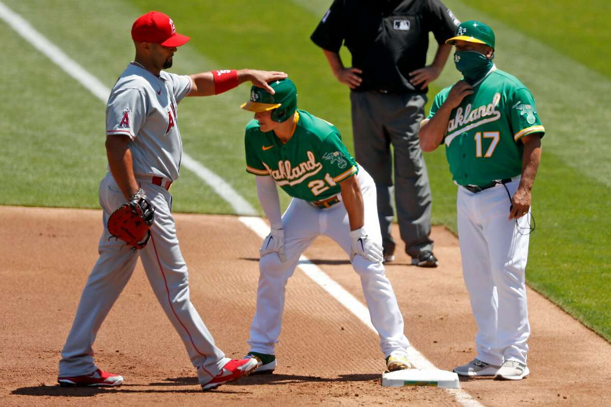 Los Angeles Angels' Albert Pujols pats Oakland Athletics' Matt Chapman on the helmet after Chapman singled in 1st inning in MLB game at Oakland Coliseum in Oakland, Calif., on Monday, July 27, 2020.