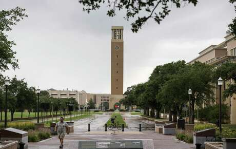 People pass through campus as the Albritton Bell Tower is seen in the background on Tuesday, July 7, 2020, at Texas A&M University in College Station.