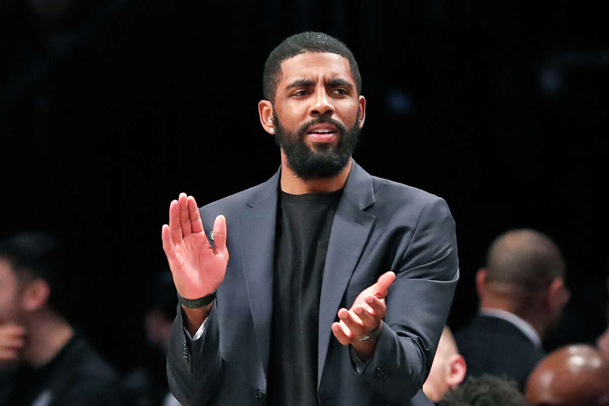 FILE - In this Tuesday, Jan. 7, 2020, file photo, injured Brooklyn Nets guard Kyrie Irving applauds his teammates from the bench during the first half of an NBA basketball game against the Oklahoma City Thunder, in New York. Irving is joining rapper Common and others for a TV special calling for action following the death of Breonna Taylor. Irving is producing a€œ#SAYHERNAME: BREONNA TAYLOR,a€ which will debut Wednesday, July 8, 2020, at 7 p.m. EDT on the PlayersTv digital and broadcast network.(AP Photo/Kathy Willens, File)