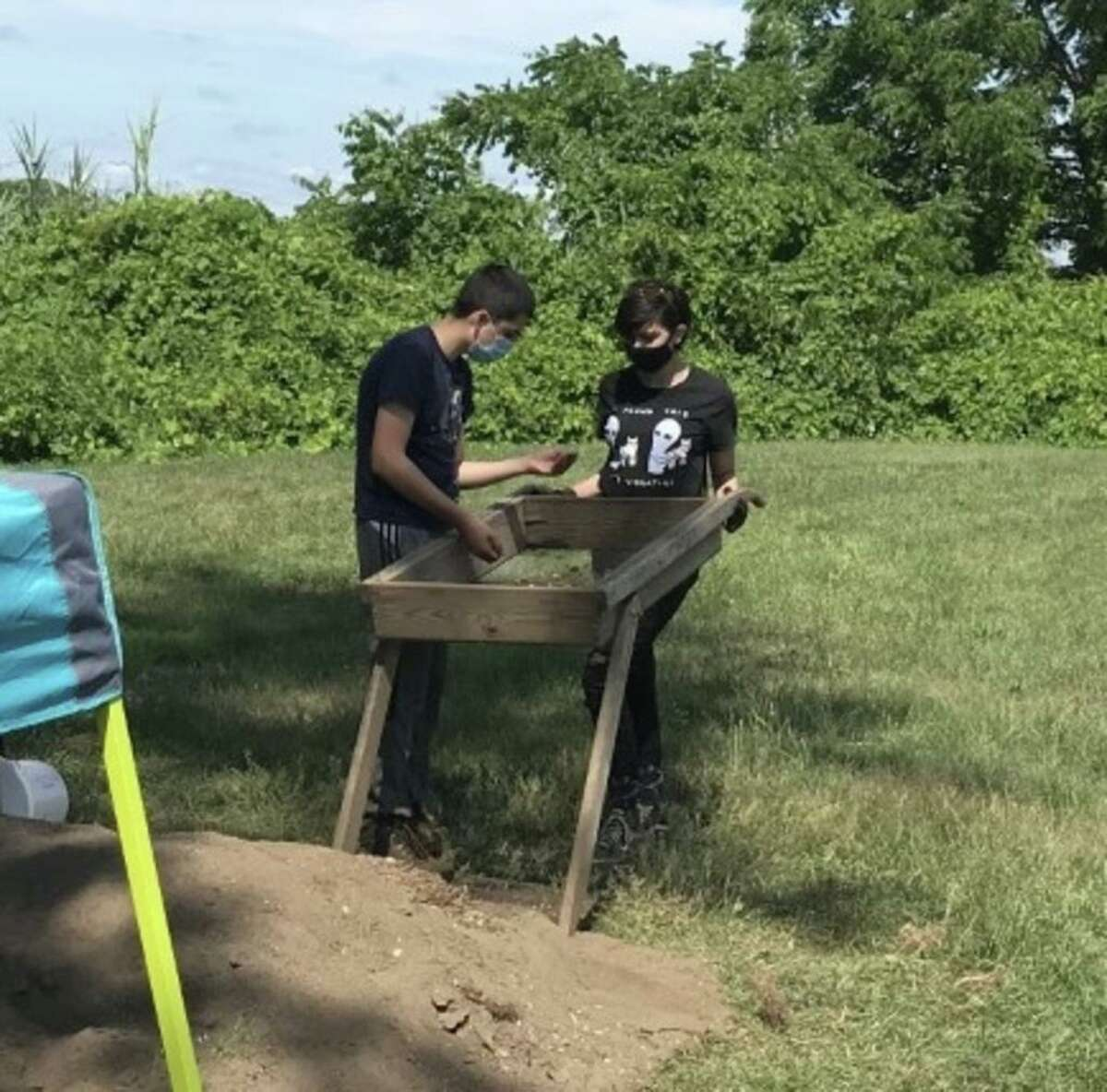 Aidan Glass and Bridget Dwyer sift through the dirt looking for artifacts.