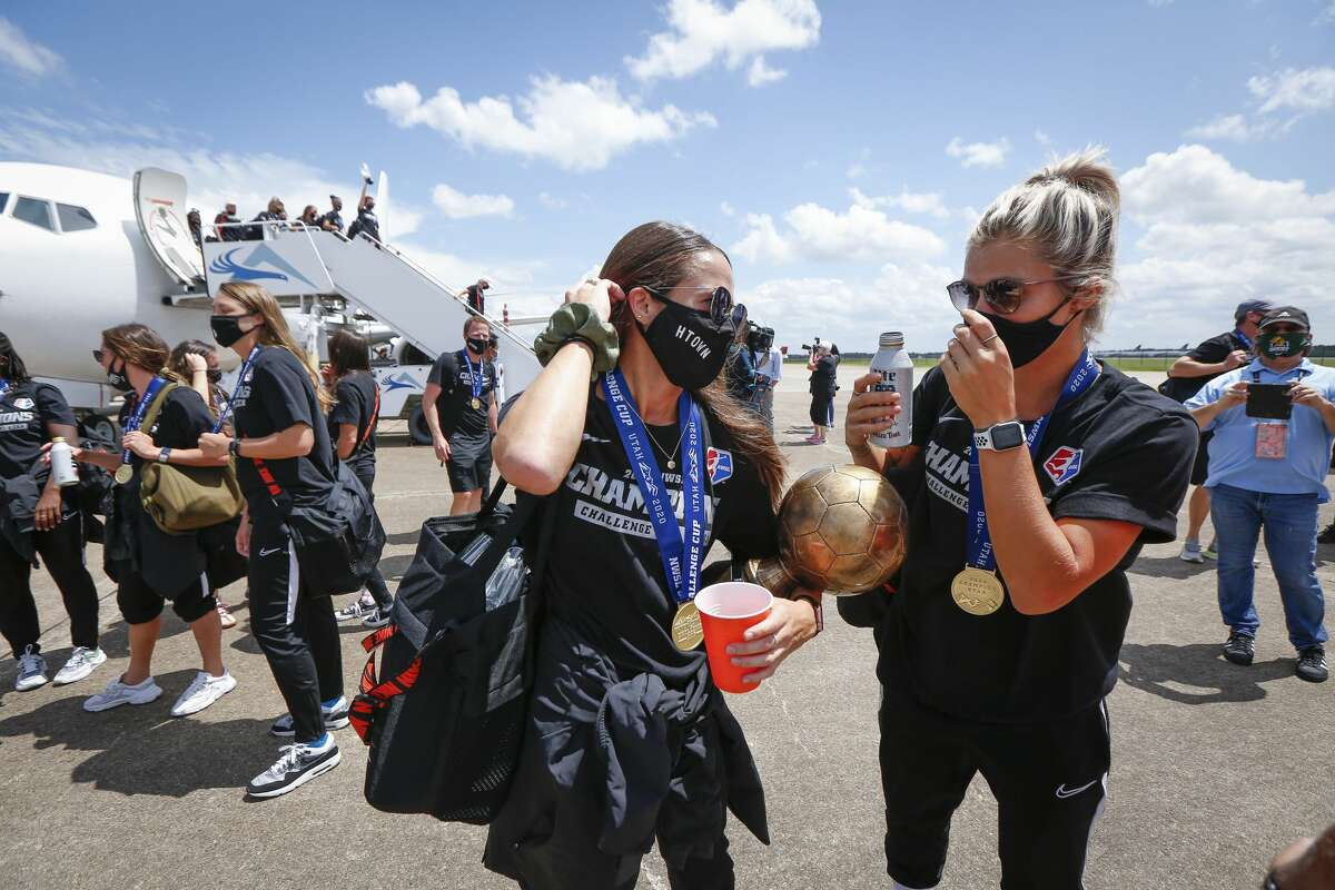 Houston Dash Shea Groom (left) holds her MVP trophy as she talks with Rachel Daly after returning home with the championship trophy at Atlantic Aviation IAH Monday, July 27, 2020, in Houston.