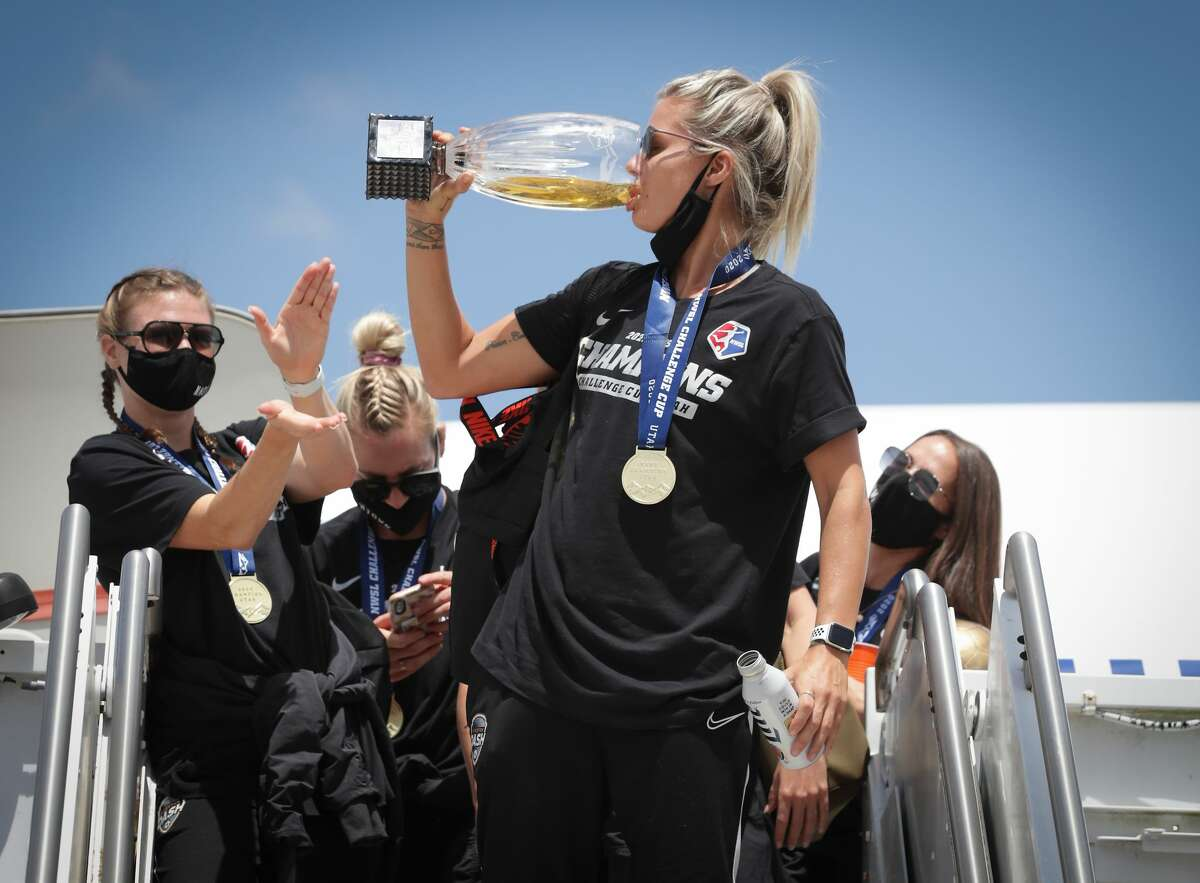 Houston Dash Rachel Daly drinks from the championship trophy after returning home at Atlantic Aviation IAH Monday, July 27, 2020, in Houston.