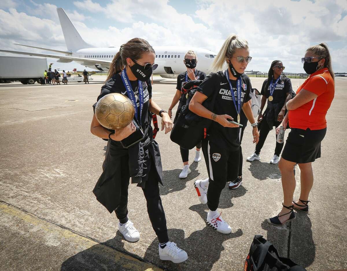 Houston Dash Shea Groom (left) holds her MVP trophy as she walks with Rachel Daly after returning home with the championship trophy at Atlantic Aviation IAH Monday, July 27, 2020, in Houston.
