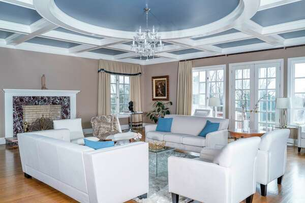 The library at 13 Aiken Road is a bright space, with a high, detailed coffered ceiling, oversized windows and French doors that open out to a patio, pool, and the four acres of grounds. The property is listed by Houlihan Lawrence for $4.25 million.