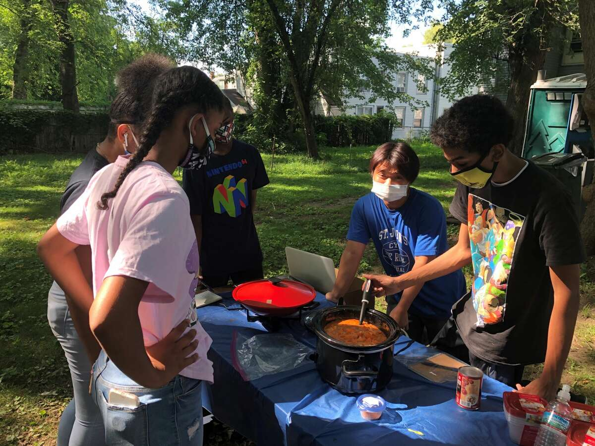 Attendees of  summer camp check on the simmering peanut soup at the Stephen and Harriet Myers Residence on Livingston Avenue in Albany on Monday, July 27, 2020 (Gary Hahn / Times Union)